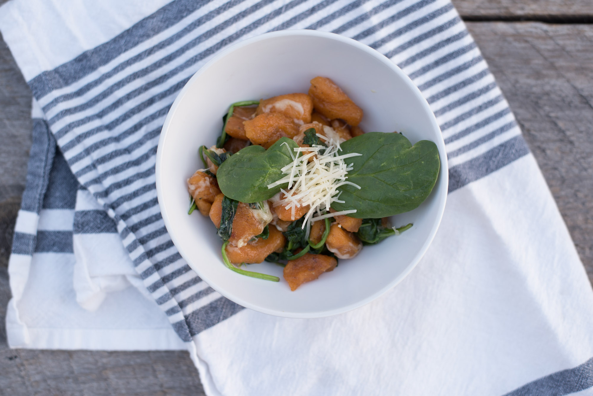 Delicious Paleo homemade Sweet Potato Gnocchi with a garlic butter spinach sauce