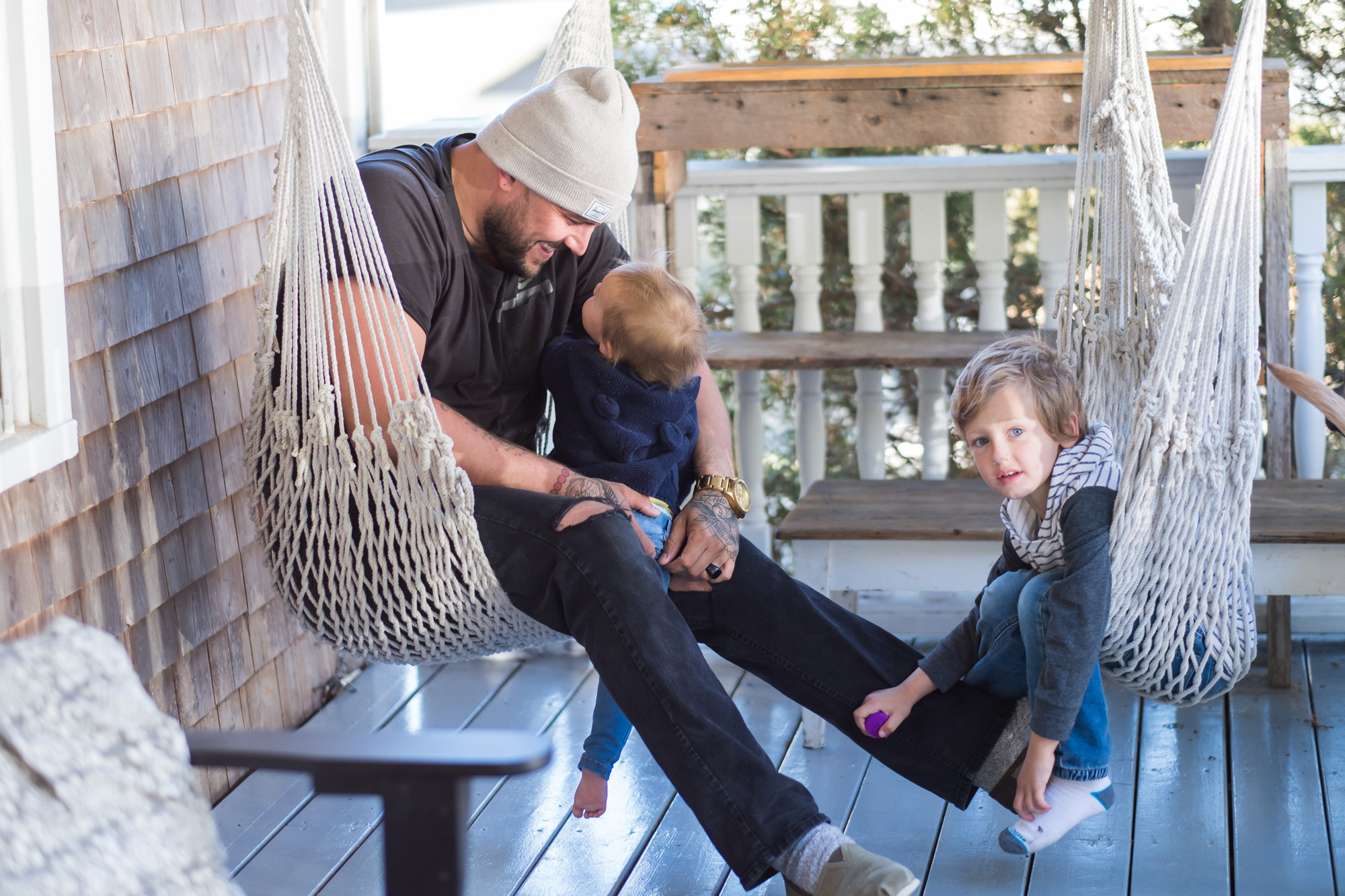 Wild Rosebuds| Family photo of Rob, Poppy and Aubrey on the porch swings