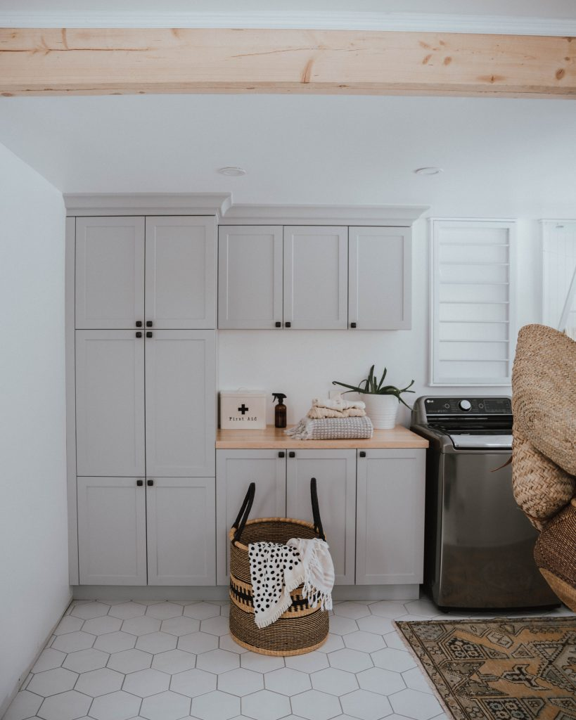 The Wild Decoelis | exposed beam in laundry room with grey cabinets
