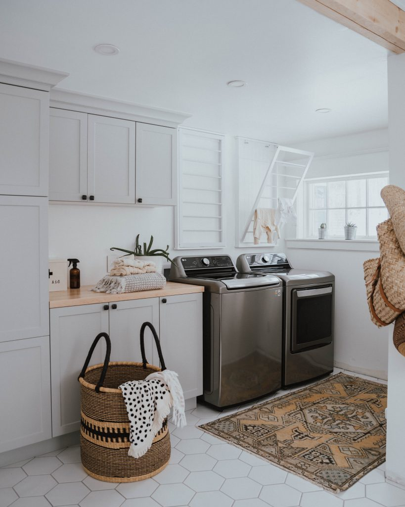 The Wild Decoelis | Laundry room makeover with grey cabinets, hexagon white tile and butcher block countertops