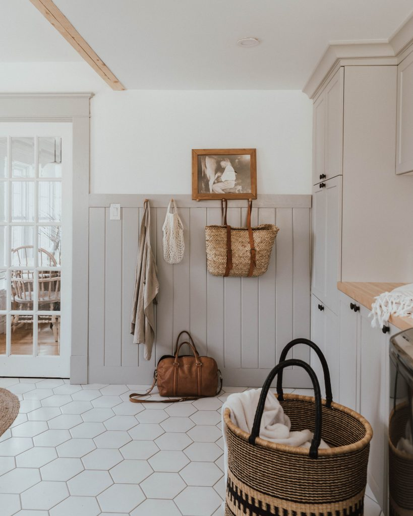 The Wild Decoelis | Everything You Want To Know About Our Traditional Farmhouse Laundry Room and Mudroom | hex white tiles, great wainscotting wall paneling vintage art