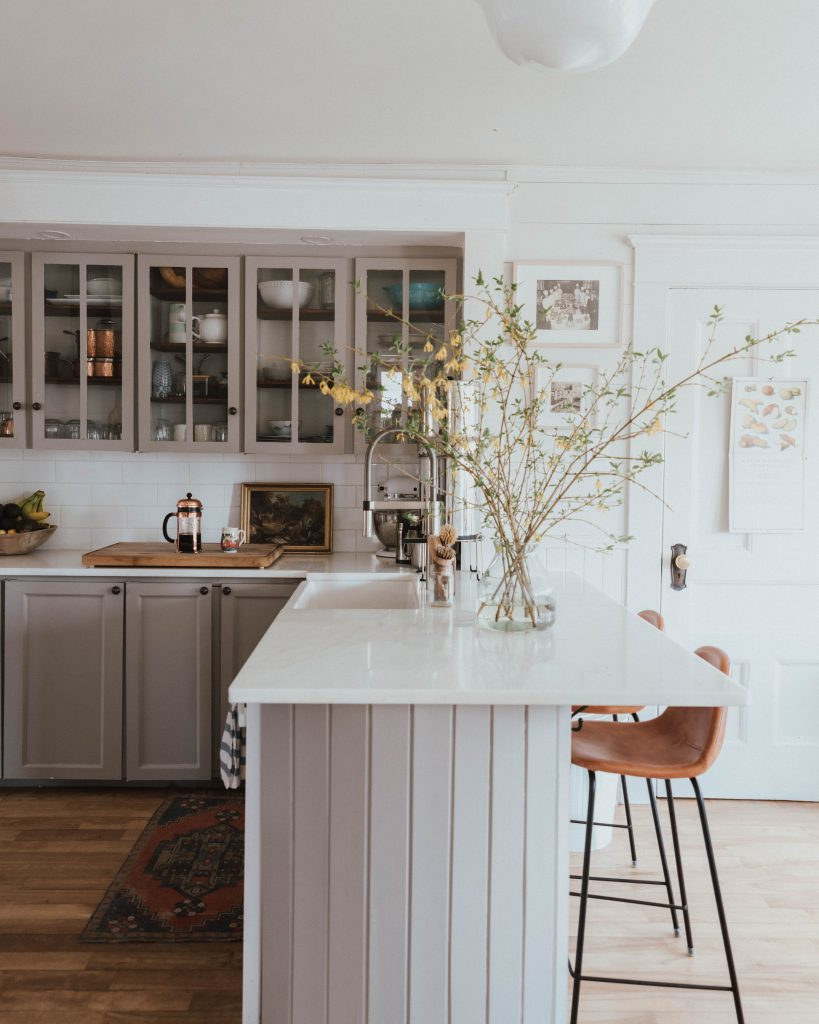 The Wild Decoelis | How to force bloom flowering trees and bushes in your home | Grey kitchen with white shiplap, marble countertops, forsythia, leather bar stools, vintage rug and vintage art.