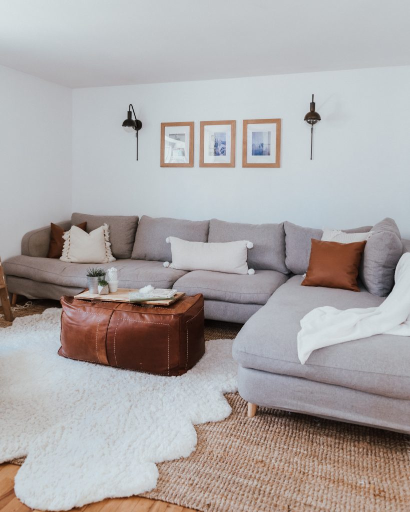 The Wild Decoelis | Our Cozy and Welcoming Family room | grey sectional, jute rug, shag sheepskin rug, leather ottoman, leather Mobilia ned chair, blanket ladder.