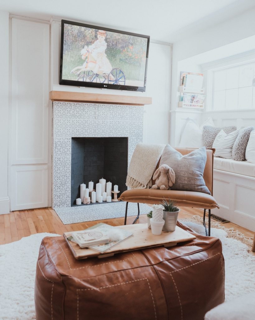 The Wild Decoelis | Our Cozy and Welcoming Family room | grey sectional, jute rug, shag sheepskin rug, leather ottoman, leather Mobilia ned chair, blanket ladder. fireplace with candles