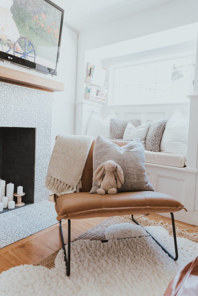 The Wild Decoelis | Our Cozy and Welcoming Family room | grey sectional, jute rug, shag sheepskin rug, leather ottoman, leather Mobilia ned chair, blanket ladder. candles in fireplace