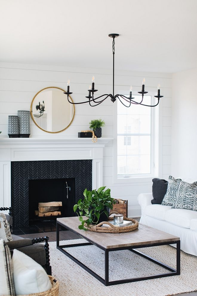 The Wild Decoelis | One Room Challenge: Our Formal Living Room | black chandelier in living room with black and white fireplace, round mirror