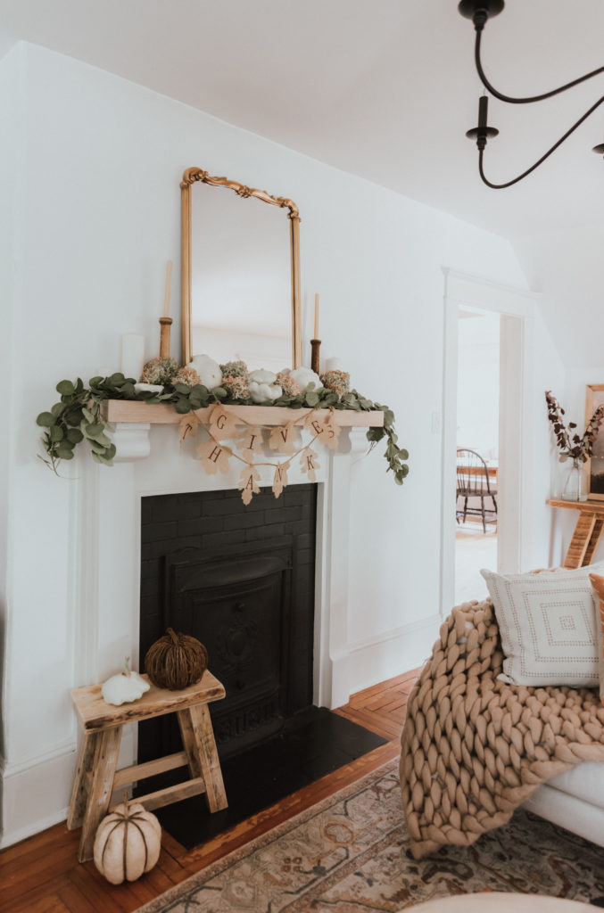 The Wild Decoelis | Fall Home Tour | mantle  decorated with faux eucalyptus bows, vintage candlesticks, gold leaf mirror, Thanksgiving banner, dried hydrangeas, and white pumpkins