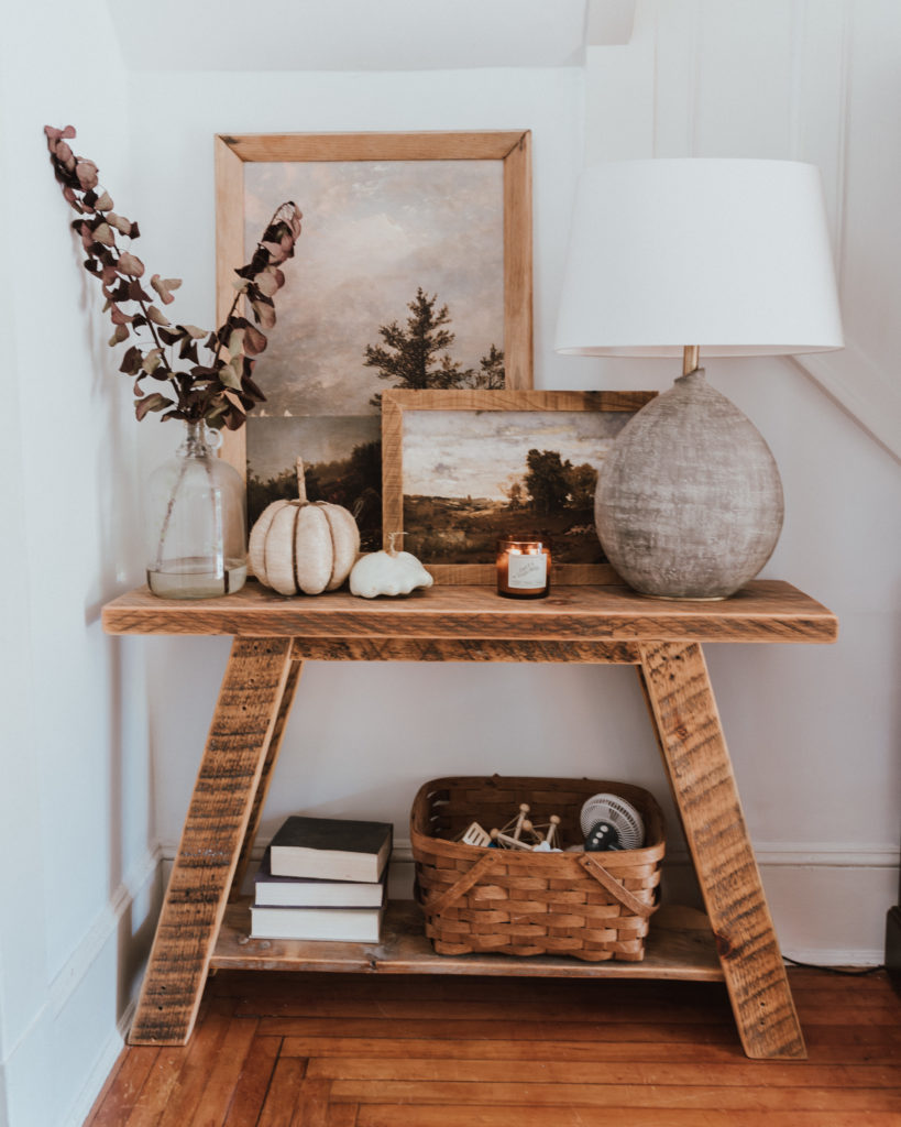 The Wild Decoelis | Fall Home Tour | DIY entry table made with reclaimed wood, Stone lamp, vintage artwork, tree branches with burgundy leaves, and white pumpkins