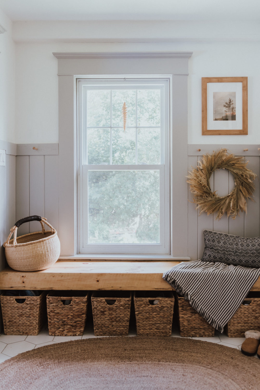 The Wild Decoelis | Fall Home Tour | gray wainscotting mudroom with built in floating bench, baskets for shoes, a throw pillow and a fall wreath on shaker peg rail