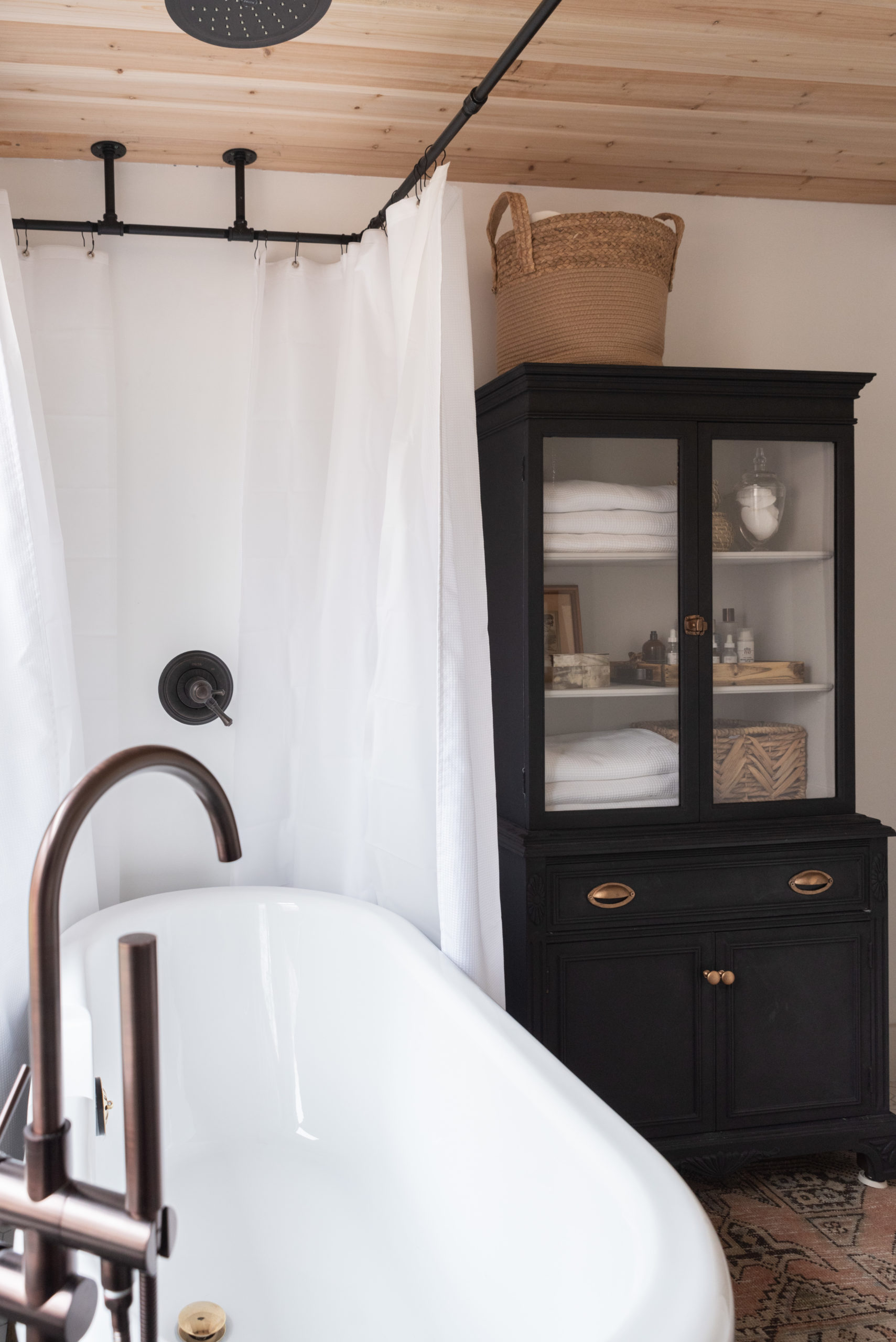 The Wild Decoelis | Our Bathroom Reno | white bathroom with gray vanity, marble hexagon floor tiles and marble countertop, black clawfoot tub, cedar plank ceiling, and an antique refinished black china cabinet used for linens