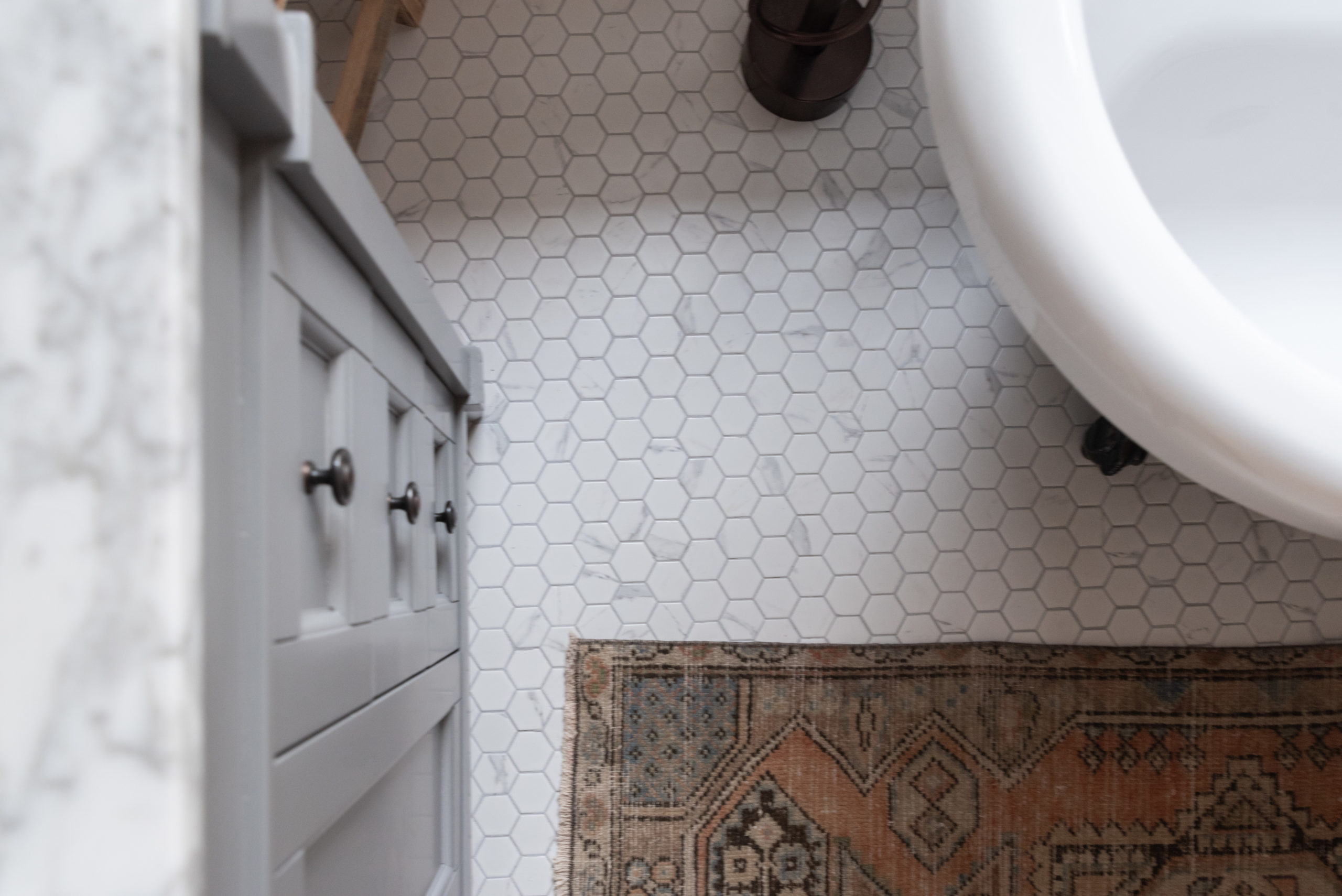 The Wild Decoelis | Our Bathroom Reno | white bathroom with gray vanity, marble hexagon floor tiles and marble countertop, black clawfoot tub, cedar plank ceiling, and an antique refinished black china cabinet used for linens vintage rug