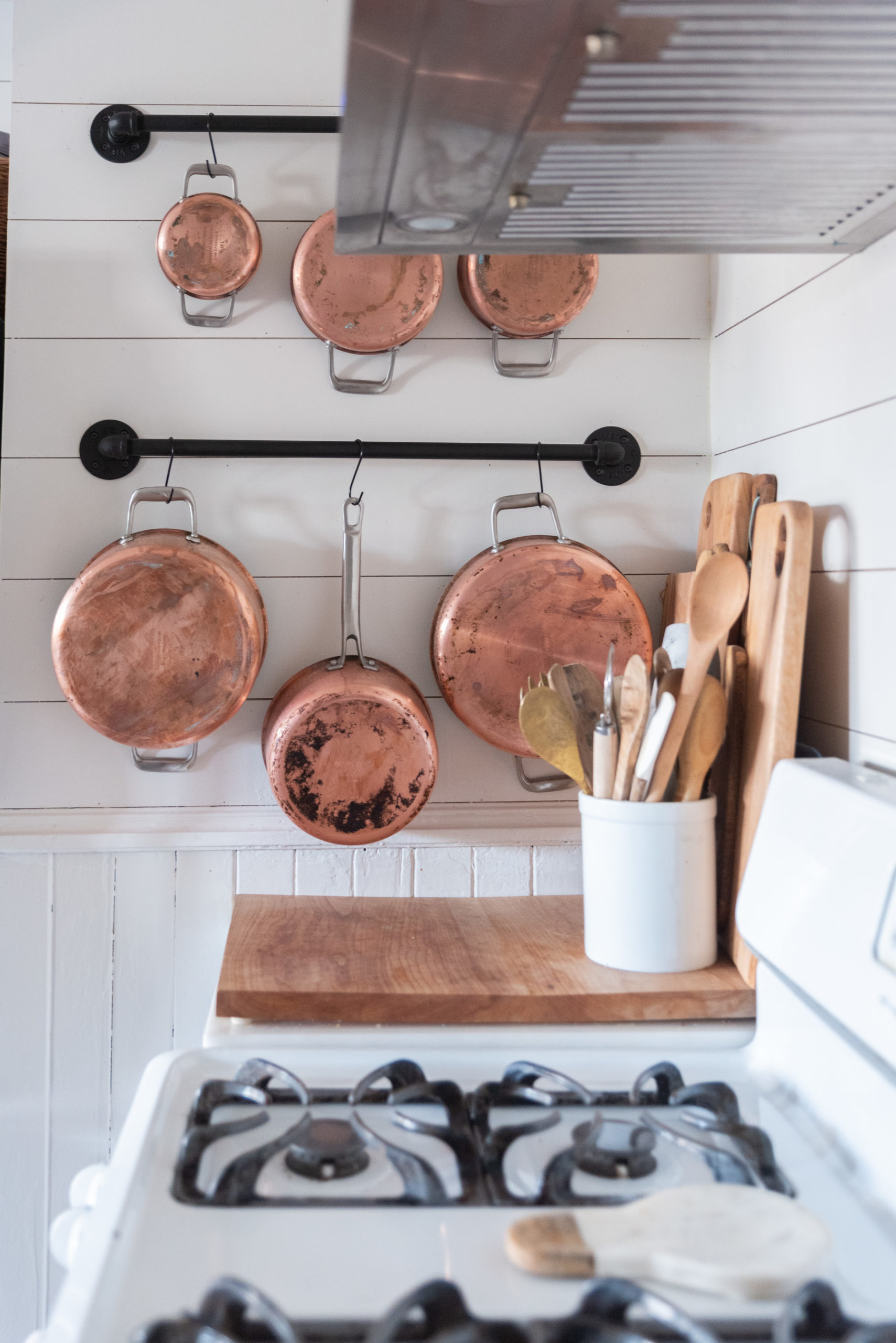 The Wild Decoelis | Our Lagostina Copper Pots: One year later How we feel about them | DIY Wall Pot Rack made of black pipe on shiplap wall in kitchen with marble countertops