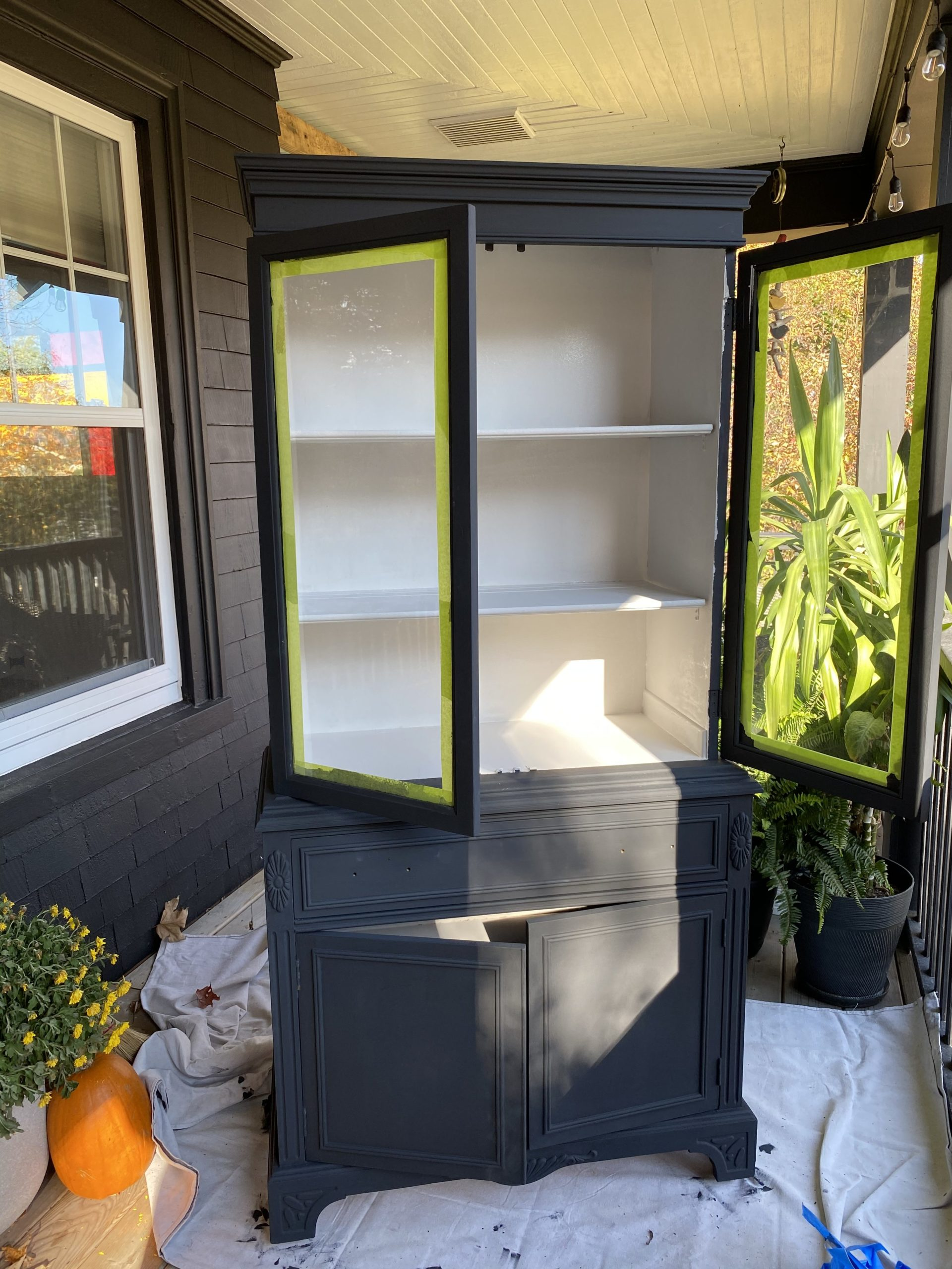 How to Refinish a China Cabinet For a Bathroom | the wild decoelis | matte black antique medicine cabinet with white grey interior in bathroom for storage with baskets and towels black clawfoot tub, vintage rug