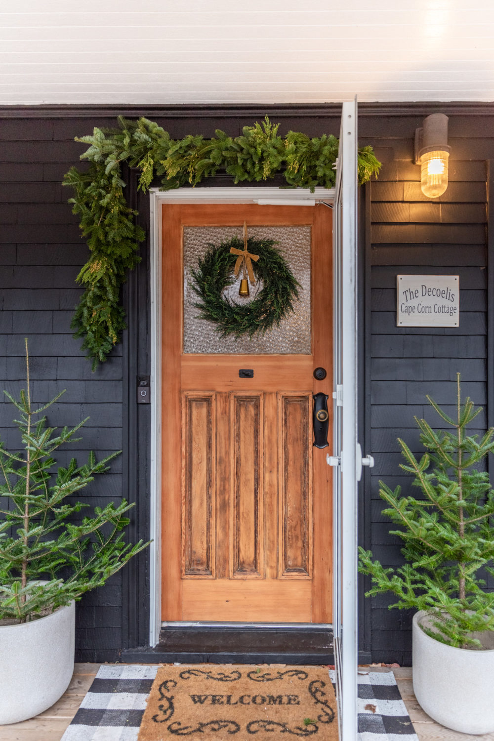 The Wild Decoelis | 2020 Holiday Home Tour | Black house with Raw wood original front door with black handle. Nautical Dock street Sconce, Trees in flower pots, garland around door and cedar wreath with twinkle lights. Buffalo plaid door mat