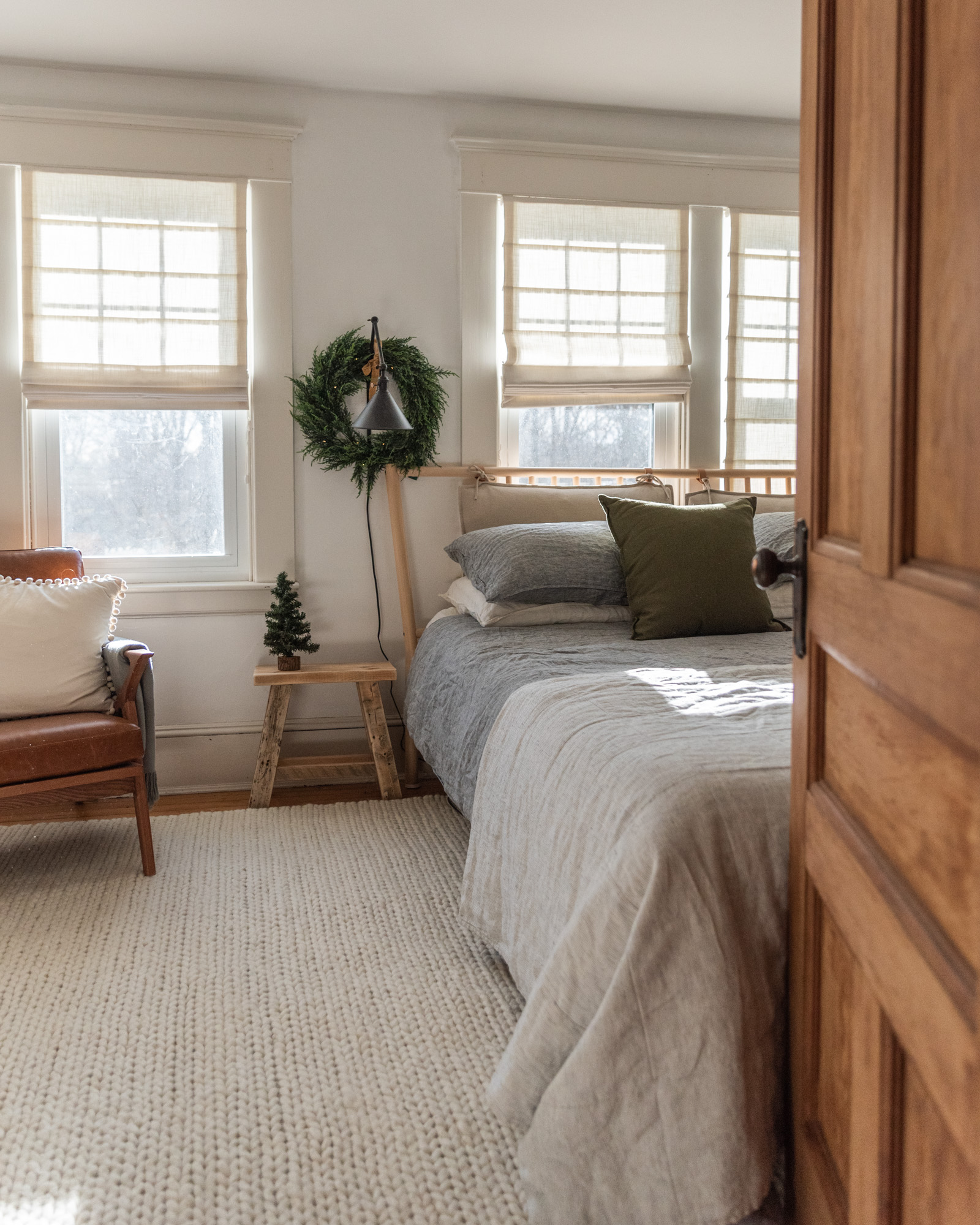 The Wild decoelis | 2020 Holiday Home Tour | Master bedroom with a king size IKEA bedframe in light wood, white linen shades, black sconces with Reese, antique side table milking stool, gray linen bedding. White braided rug USA Leather chair