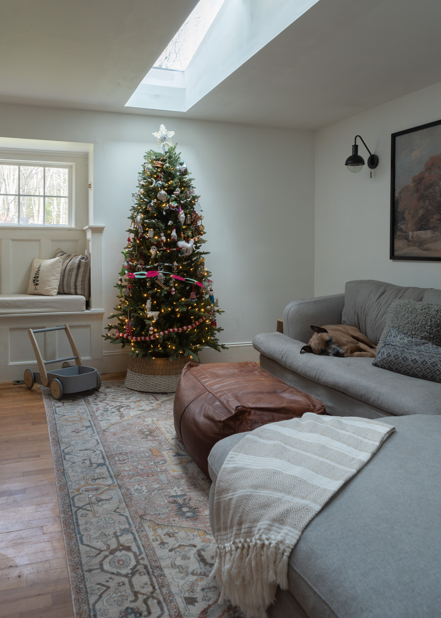 The Wild decoelis | 2020 Holiday Home Tour | Family room christmas tree with collection of ornaments and paper chain, heather gray sectional Rugs USA medallion rug leather pouf ottoman window seat and skylights