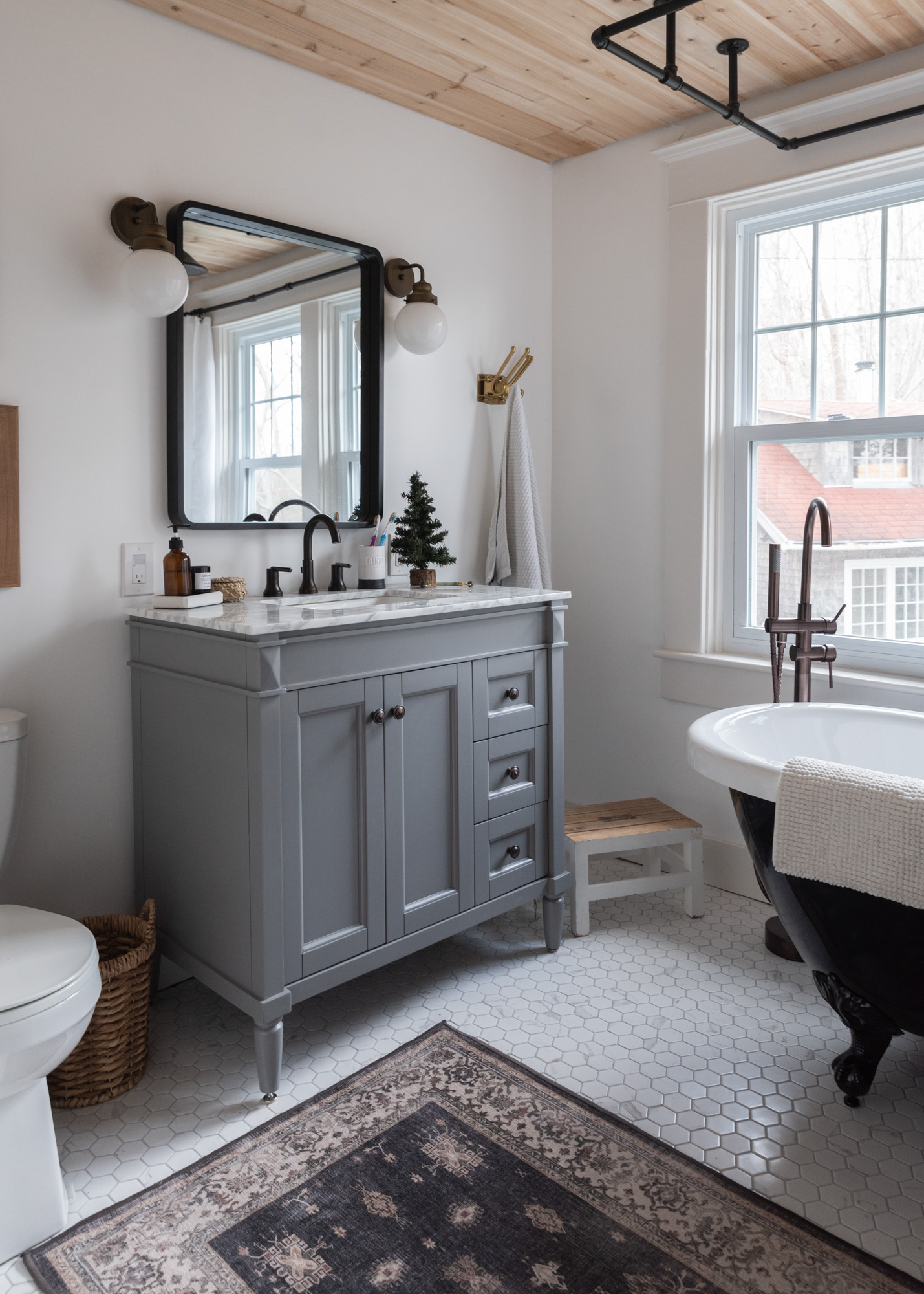 The Wild decoelis | 2020 Holiday Home Tour | Gray vanity with marble countertop, marble hexagon floor tile, rugggable Rug, black clawfoot tub gold fixtures