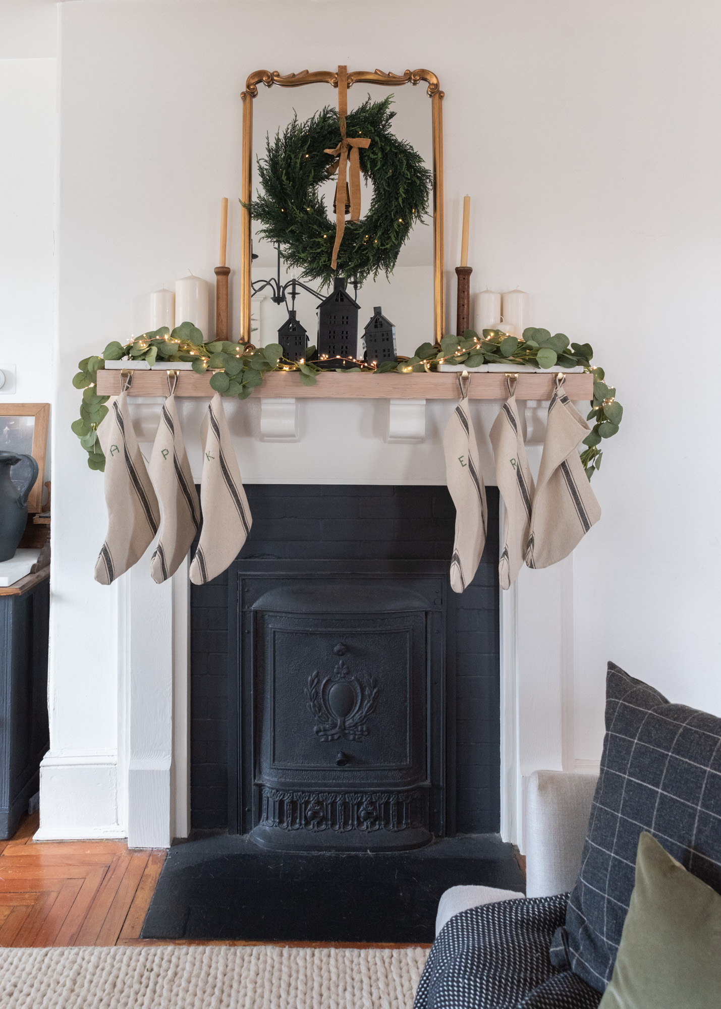 The Wild decoelis | 2020 Holiday Home Tour | Century home fireplace with Summer cover, black white and raw wood mantle, Flower sack handmade stockings with embroidered initials, twinkle lights, black houses, eucalyptus garland