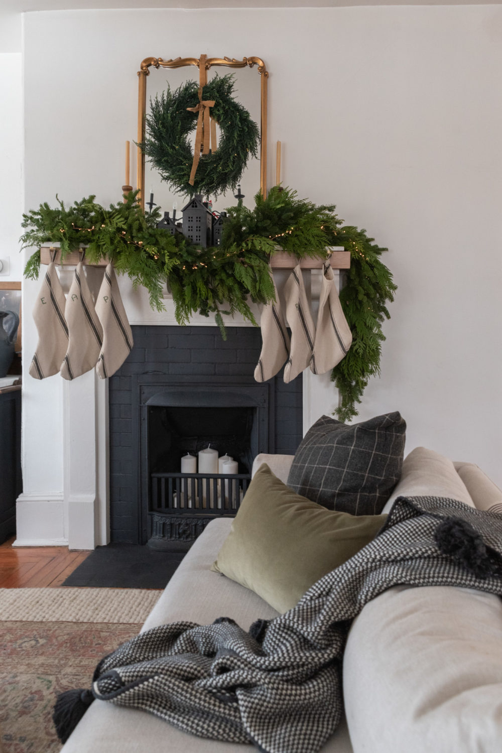 The Wild Decoelis | How To Make Flour Sack Stockings | sewing instructions | fresh fir and cedar garland on fireplace mantle with twinkle lights. Antique coal burning fireplace with candles inside. Gold mirror and cedar wreath with gold ribbon