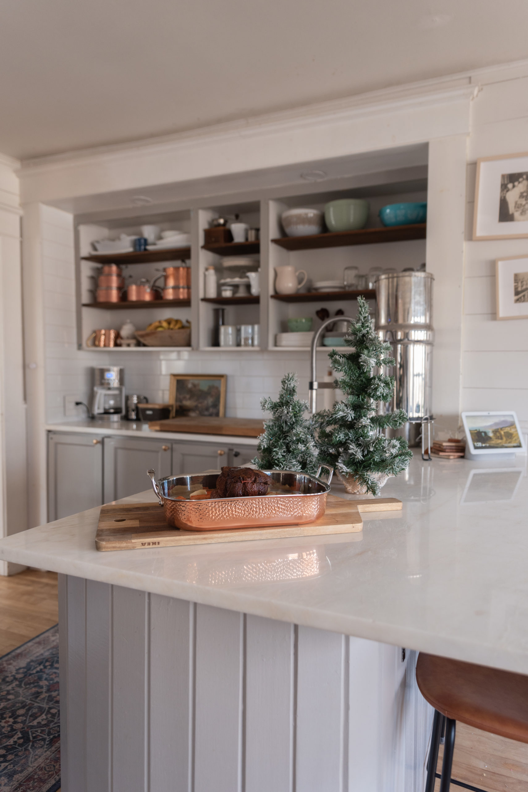 The Wild Decoelis | Holiday Home Tour | Gray kitchen with open shelving, Christmas decorations and white marble countertops