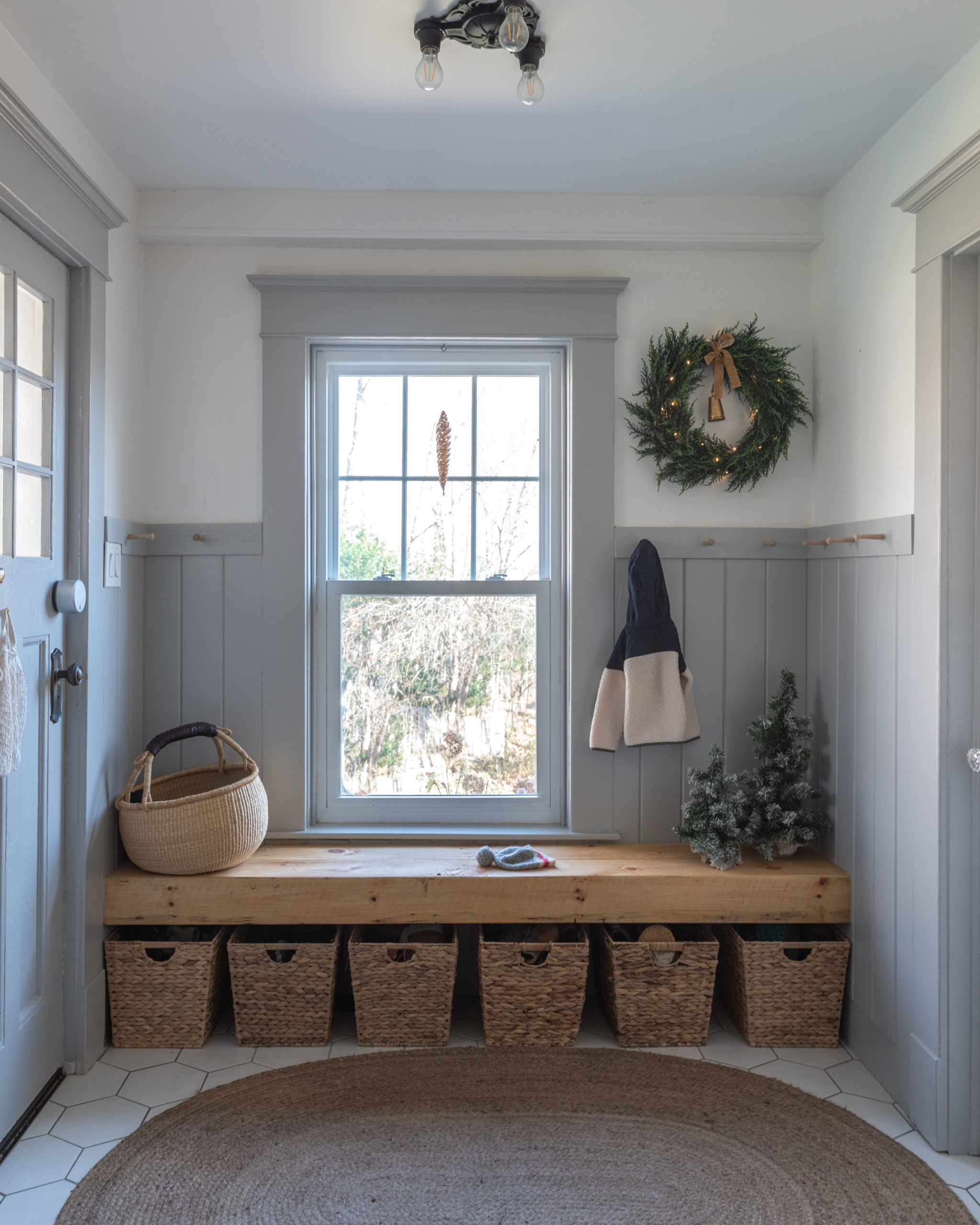 The Wild decoelis | 2020 Holiday Home Tour | Mud room with gray wainscotting and shaker peg rail, floating wood bench, baskets for shoes, mini trees and cedar wreath, traditional farmhouse
