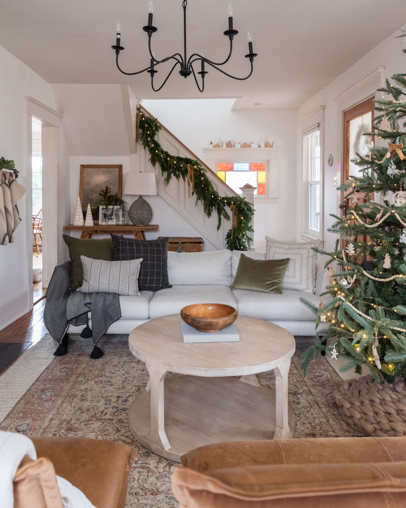 The Wild decoelis | 2020 Holiday Home Tour | Stair garland made out of pine and cedar with gold bows and twinkle lights. White couch with wool throw pillows, vintage wool rug layered over braided wool rug