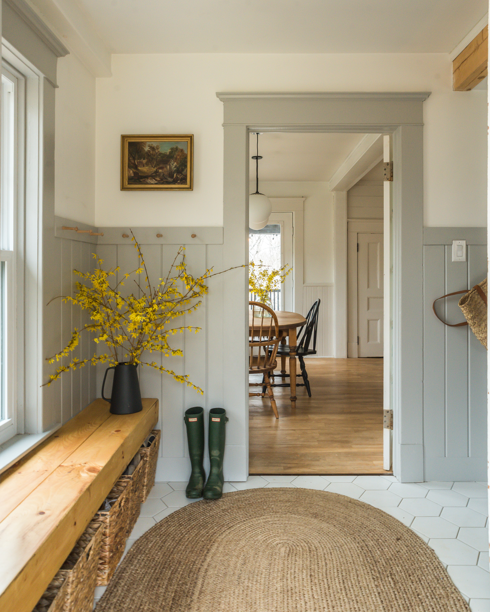 The wild Decoelis / Design Consultations ? gray wainscotting in mudroom with built in bench and hexagon tile. antique art.