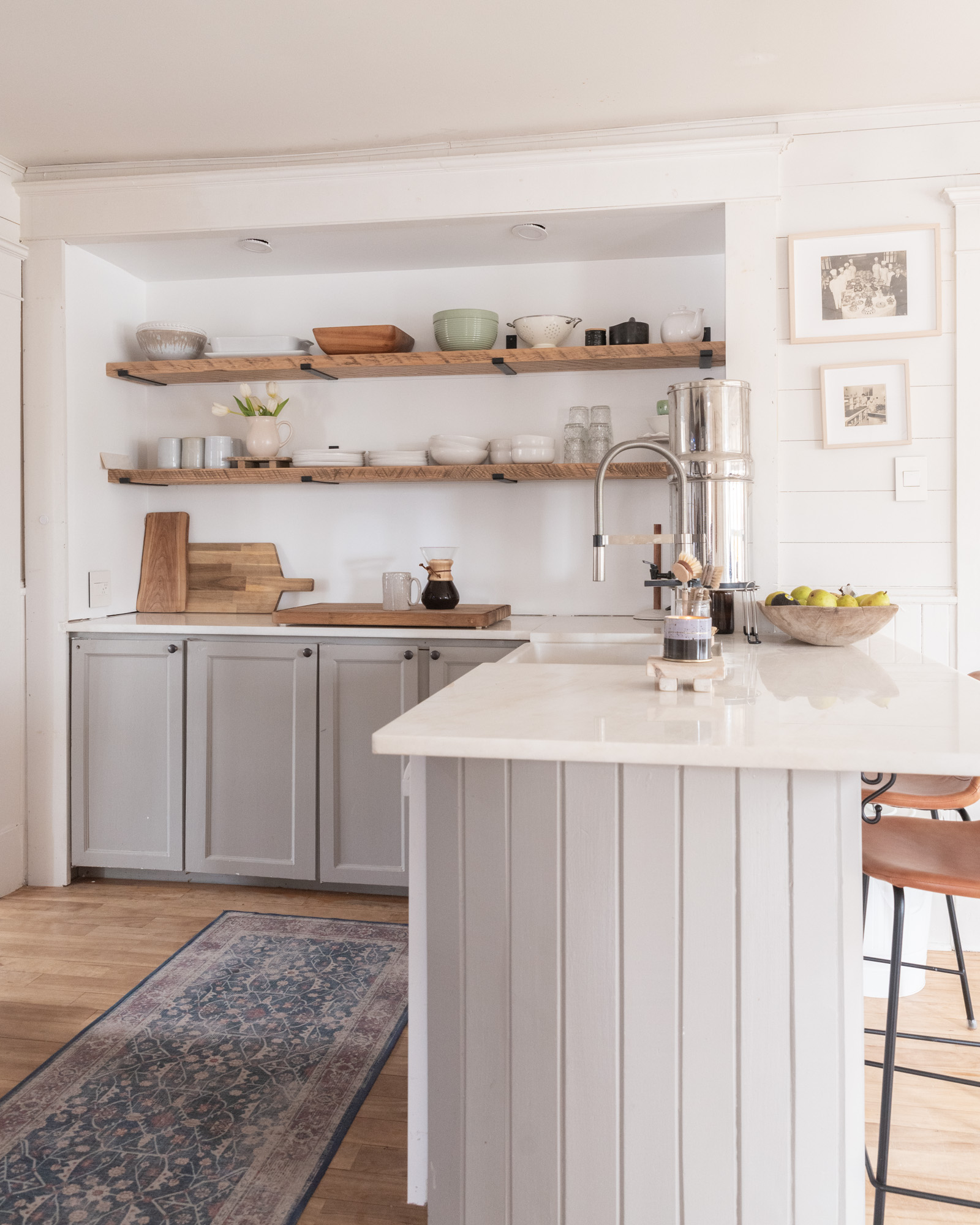 The Wild Decoelis | Kitchen shelves rough sawn with black iron brackets minimal reclaimed wood and white ceramics. grey kitchen cabinets white walls