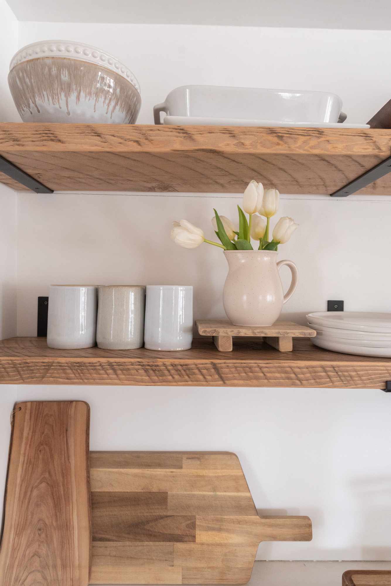 The Wild Decoelis | Kitchen shelves rough sawn with black iron brackets minimal reclaimed wood and white ceramics. tulips on stand