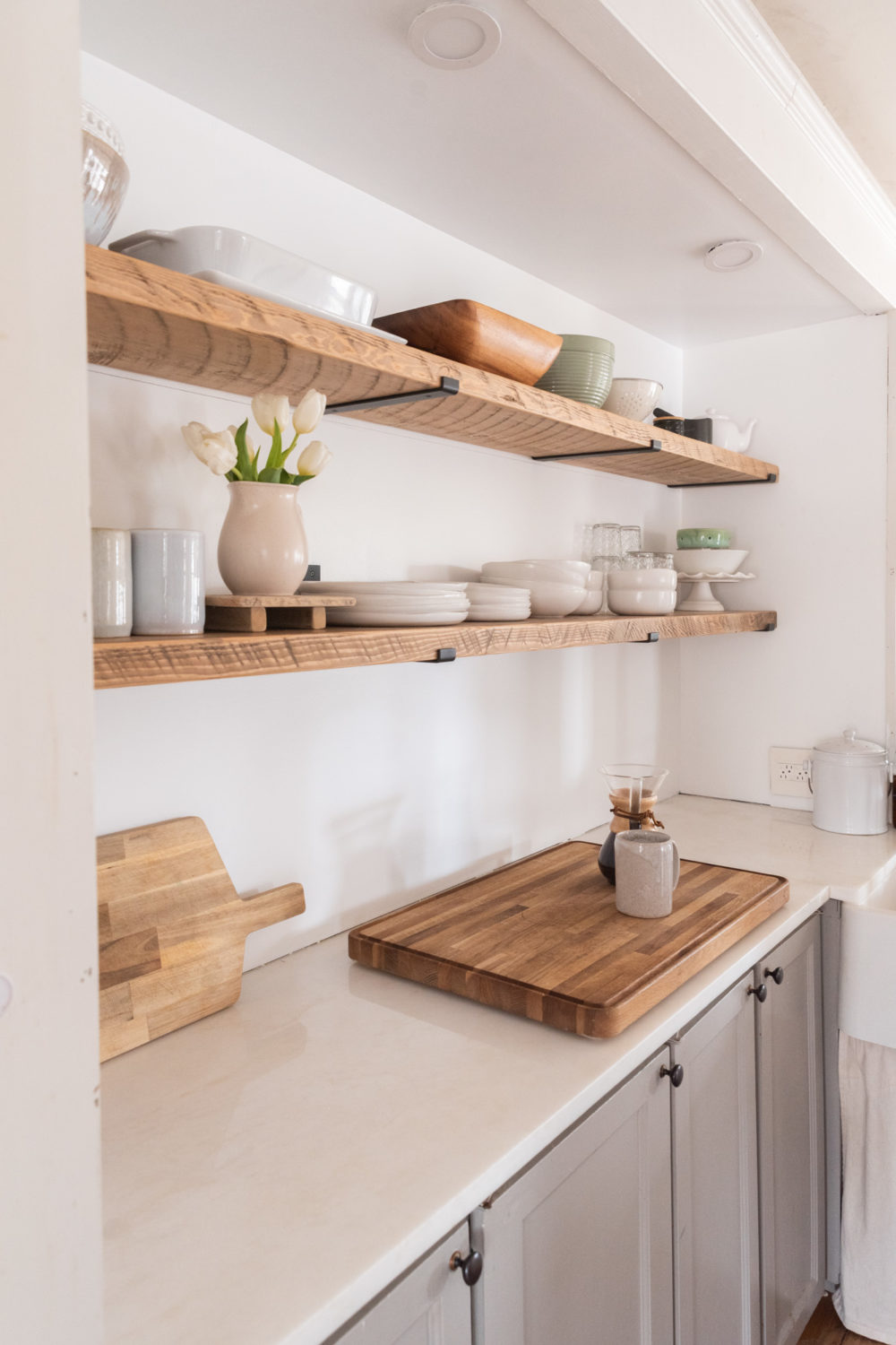 The Wild Decoelis | Kitchen shelves rough sawn with black iron brackets minimal reclaimed wood and white ceramics.