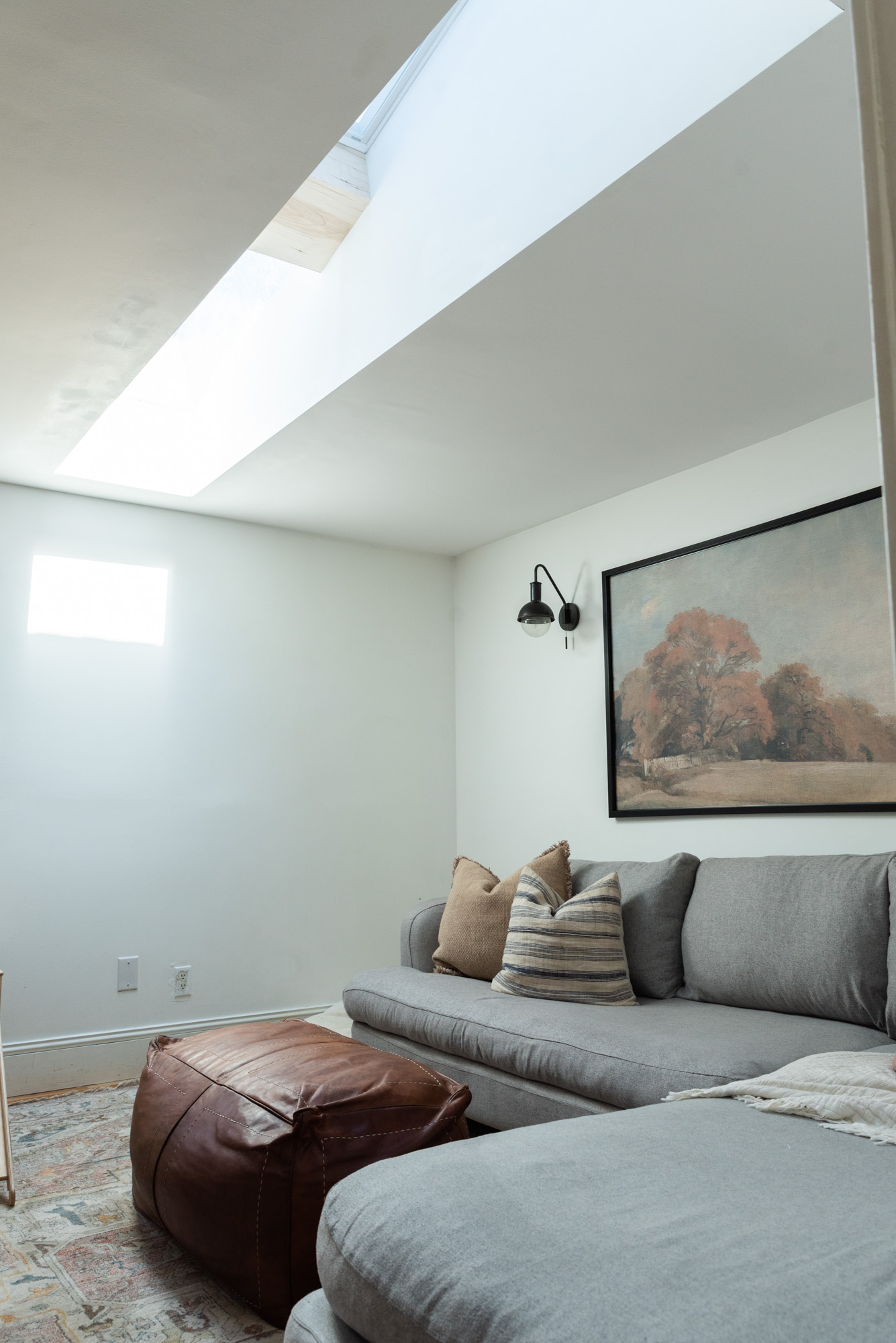 Getting More Light With Velux | The Wild Decoelis | skylights in family room with grey sectional and leather ottoman