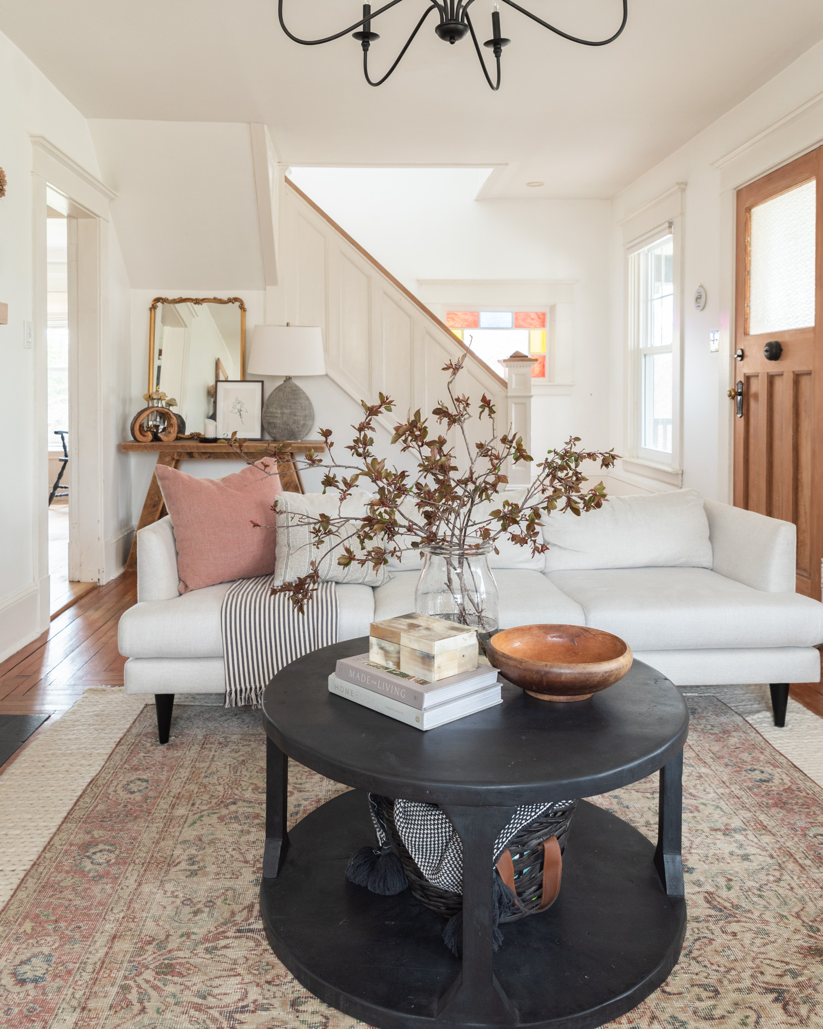 The Wild Decoelis | Four ways To Refresh Your Home For Spring | black round coffee table, cream sofa, vintage rug, flowering branches, wool rug, white craftsman living room.