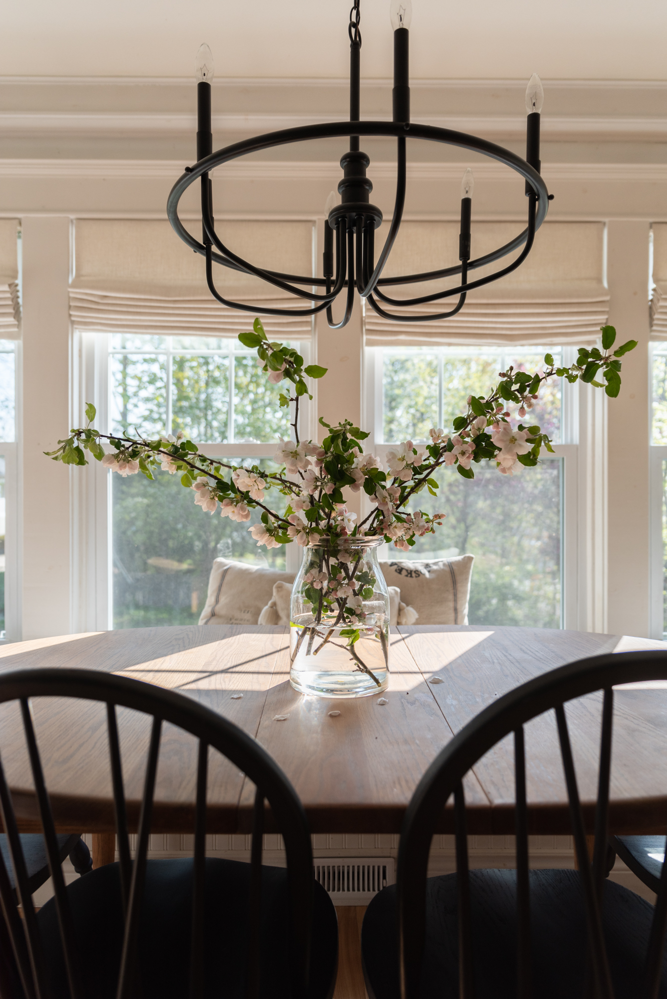 the wild decoelis | apple blossom branches in the house as decorations. Built in bench, refinished wood floors, black chairs, baskers, black vase, black chandelier, vintage art.