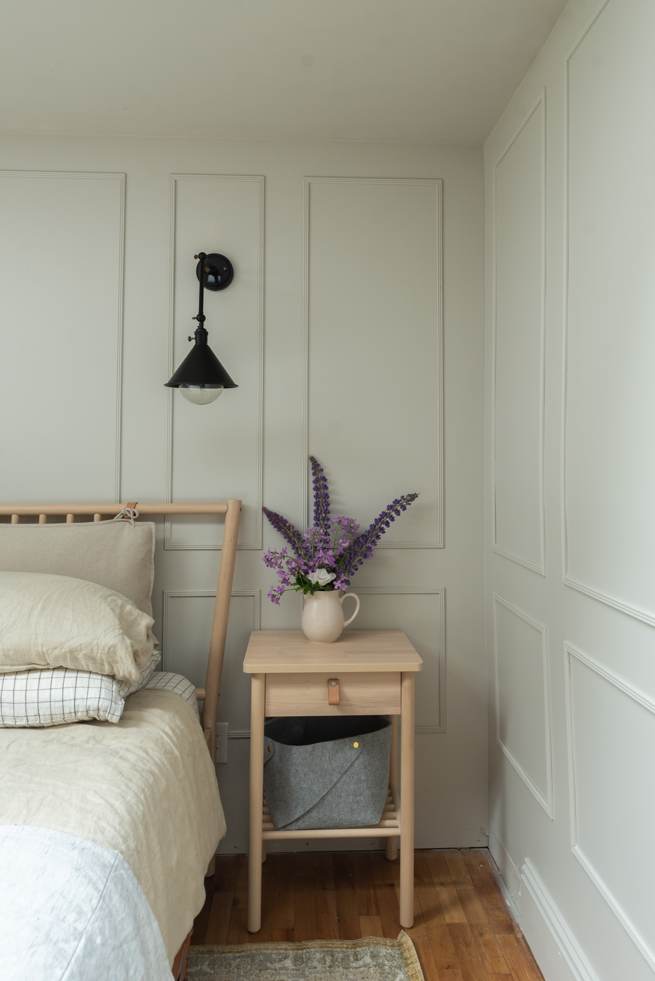 The Wild Decoelis | Our New Primary Bedroom | SW Agreeable Gray bedroom with Picture frame moulding, black sconces, raw wood bedrframe and natural linen bedding, CLJx loloi rug