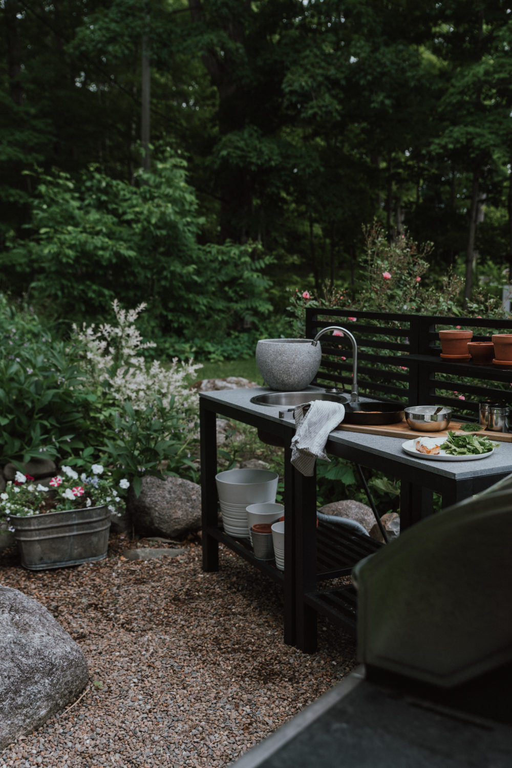 The Wild Decoelis | Out door Kitchen By Hauser on pea stone patio in the middle of a garden